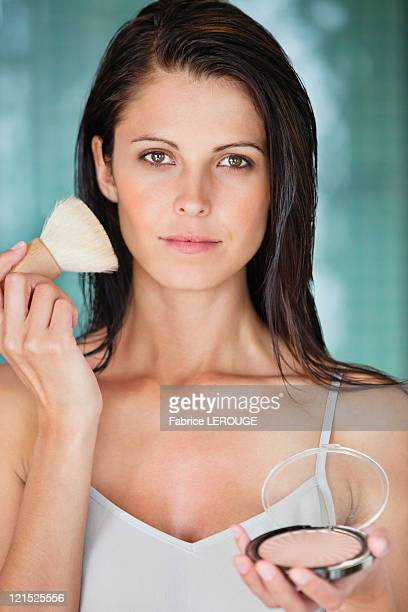 Portrait of a woman applying powder compact on her face