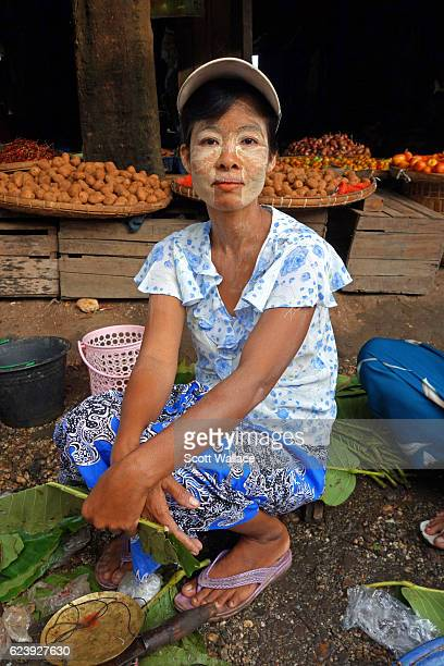 Portrait of a woman as she sells fruits and vegetables at an outdoor market Pyay Myanmar 2013 She wears thanaka paste on her face a treatment...