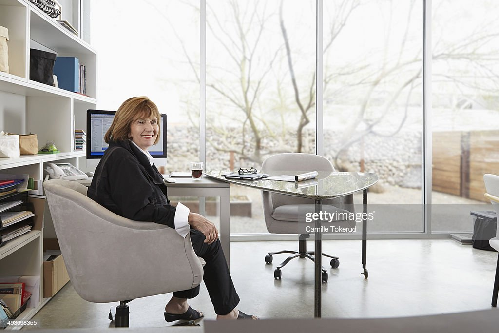 Portrait of a woman at home office smiling : Stock Photo