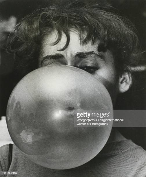 Portrait of a woman blowing a bubble gum bubble in a Greenwich Village cafe New York ca 1956 Photo by Weegee /International Center of...