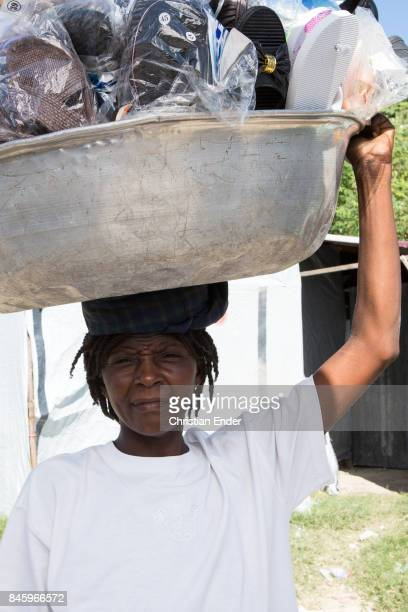 PortauPrince Haiti December 09 2012 Portrait of a woman carrying a bucket with sandals on their head probably to sell them in the refugee camp Parc...