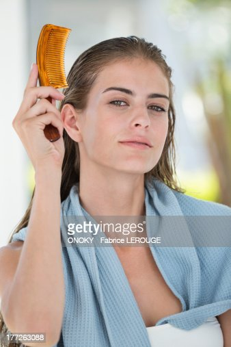 Portrait of a woman combing her hair : Stock Photo