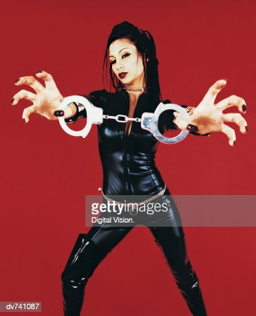Portrait of a Woman Dressed in a Catsuit Holding Handcuffs