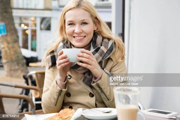 Portrait of a woman drinking coffe, sitting in outdoor pavement cafe.