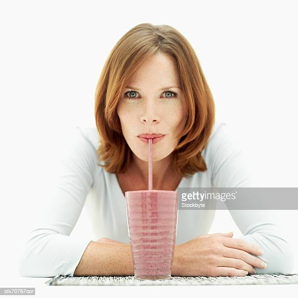 Portrait of a woman drinking juice with a straw