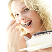 portrait of a woman eating a cheesecake with blueberry garnish