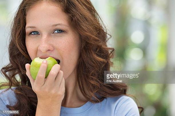 Portrait of a woman eating a green apple