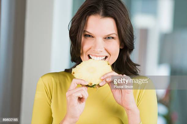 Portrait of a woman eating a slice of pineapple