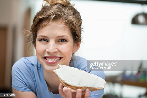 Portrait of a woman eating toast with cream spread on it