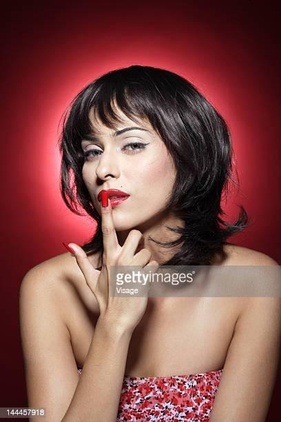 Portrait of a woman, finger on lips