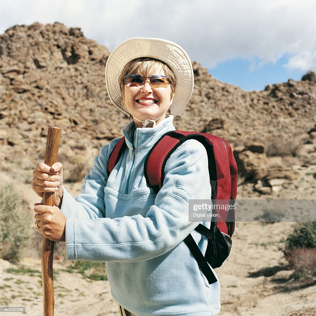 Portrait of a Woman Hiking and Using a Walking Stick in An Arid Landscape