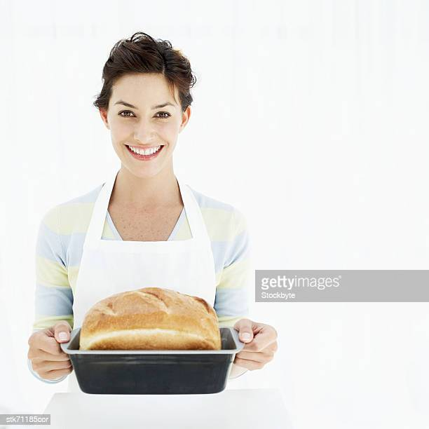 portrait of a woman holding a baking tray with freshly baked bread