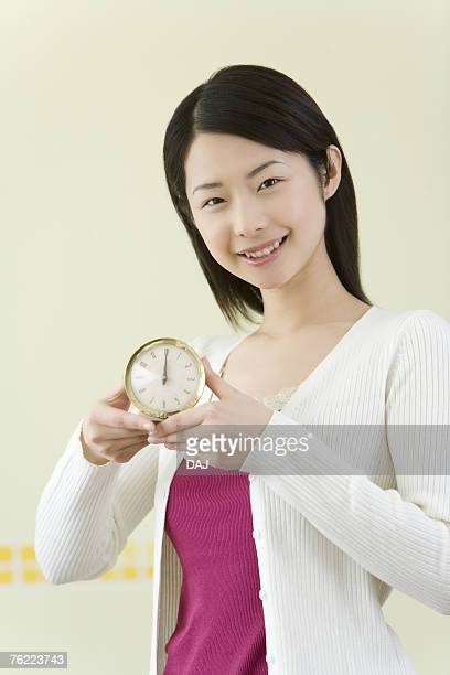 Portrait of a woman holding a clock, smiling and looking at camera, front view