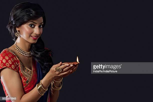 Portrait of a woman holding a diya