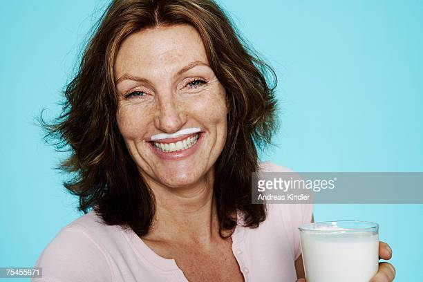 Portrait of a woman holding a glass of milk with cream on her mouth.