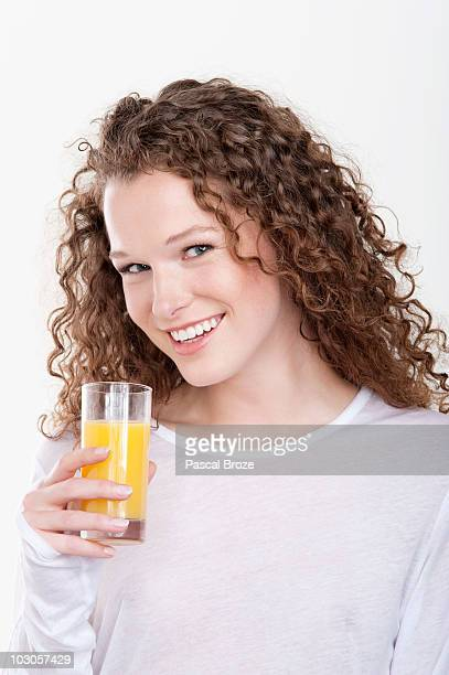 Portrait of a woman holding a glass of orange juice