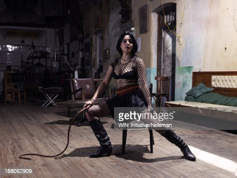 Portrait of a woman holding a whip while sitting on a chair