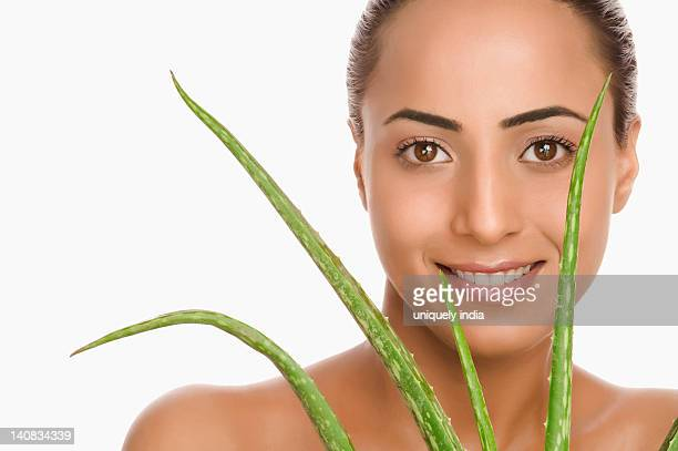 Portrait of a woman holding an Aloe Vera plant