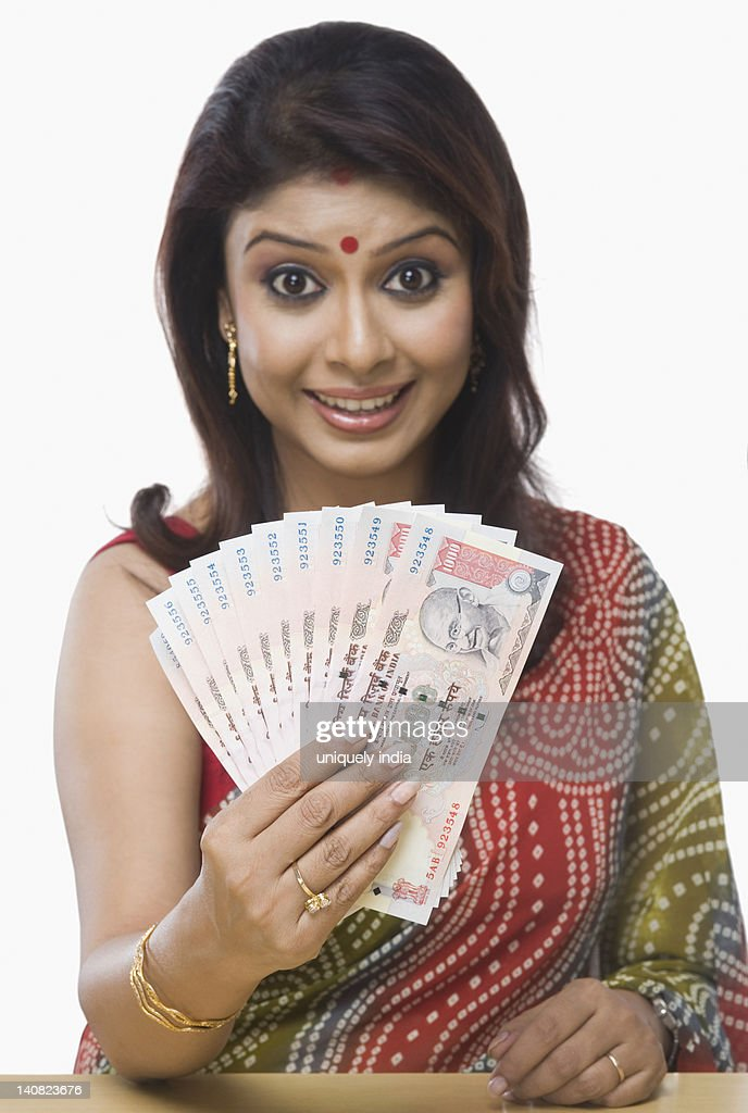 Portrait of a woman holding Indian one thousand rupee notes : Stock Photo