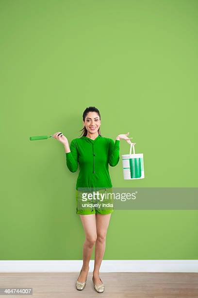 Portrait of a woman holding paint roller and paint can