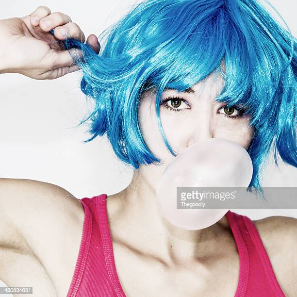 Portrait of a Woman in blue wig blowing bubblegum bubble