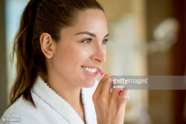 Portrait d'une femme dans la salle de bain se brosser ses dents