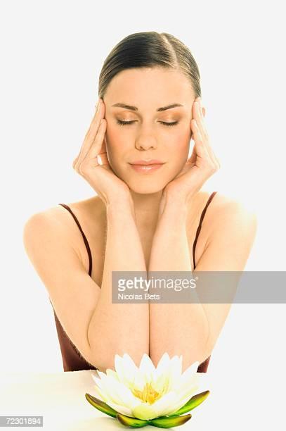 Portrait of a woman in Zen attitude, shut eyes, water lily (studio)