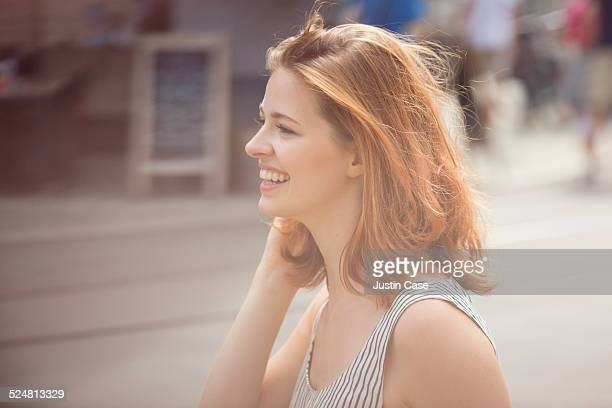 portrait of a woman laughing in the sunny city