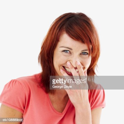 portrait of a woman laughing with her hand over her mouth : Stock Photo