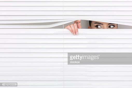 Portrait of a woman looking through out the blinds. : Stock Photo