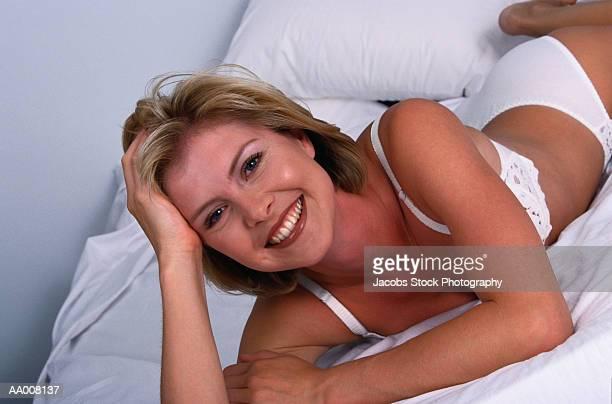 Portrait of a Woman Lying in Bed in Her Underwear