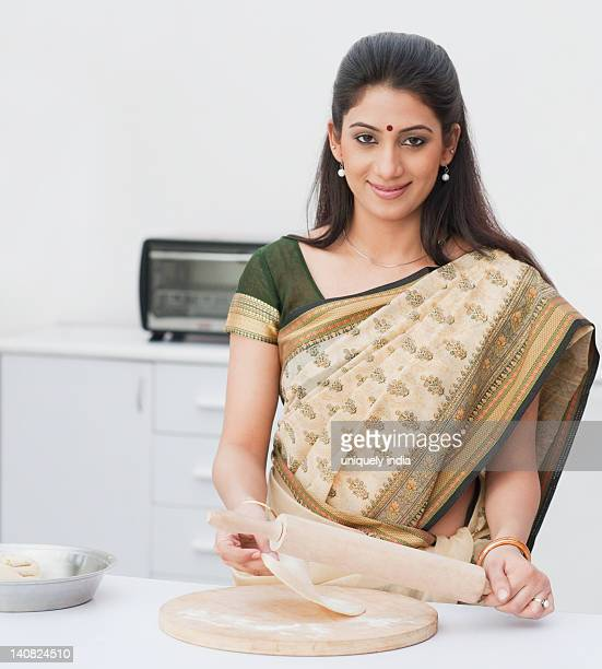 Portrait of a woman making chapatti in a kitchen