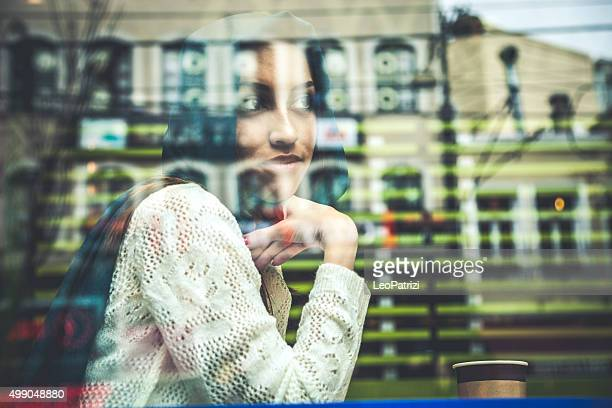 Ritratto di una donna sulla finestra di un cafe