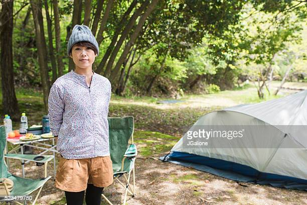 Portrait of a woman outside her tent at a campsite