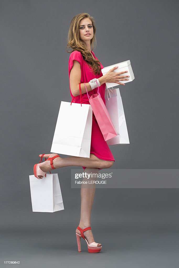 Portrait of a woman posing with shopping bags : Stock Photo