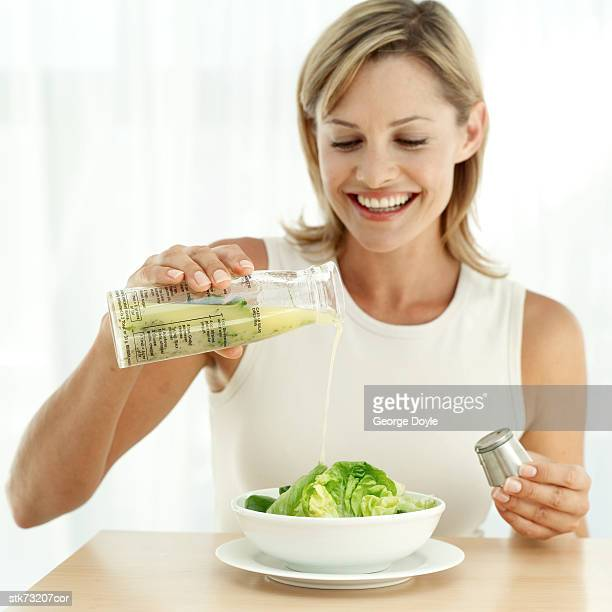 portrait of a woman pouring dressing on a bowl of salad