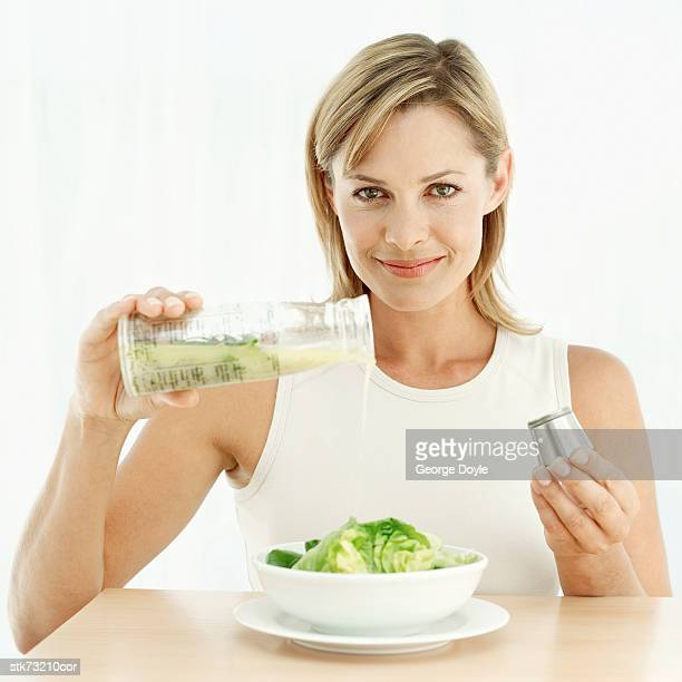 portrait of a woman pouring olive-oil over lettuce in a bowl