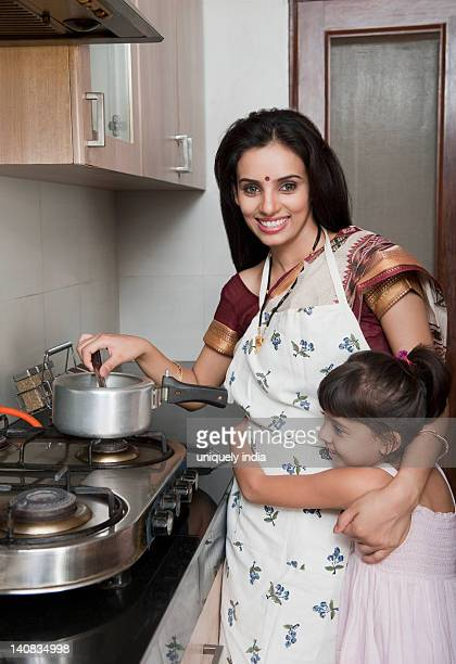 Portrait of a woman preparing food in the kitchen with her daughter
