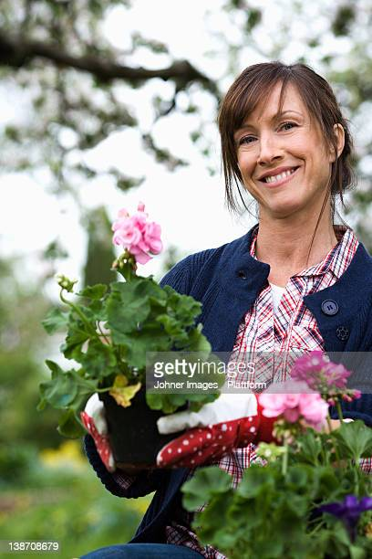 Portrait of a woman setting flowers in a pot.