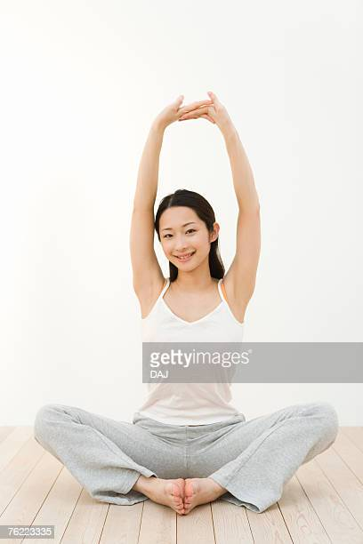 Portrait of a woman sitting cross-legged and stretching arms, front view, white background