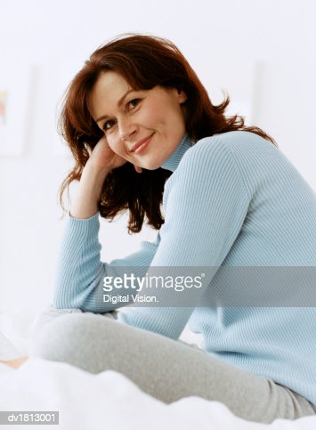 Portrait of a Woman Sitting on a Bed : Stock Photo