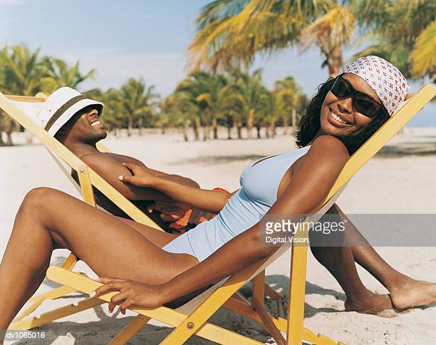 Portrait of a Woman Sitting on the Beach on a Deck Chair in Front of a Man on a Deck Chair