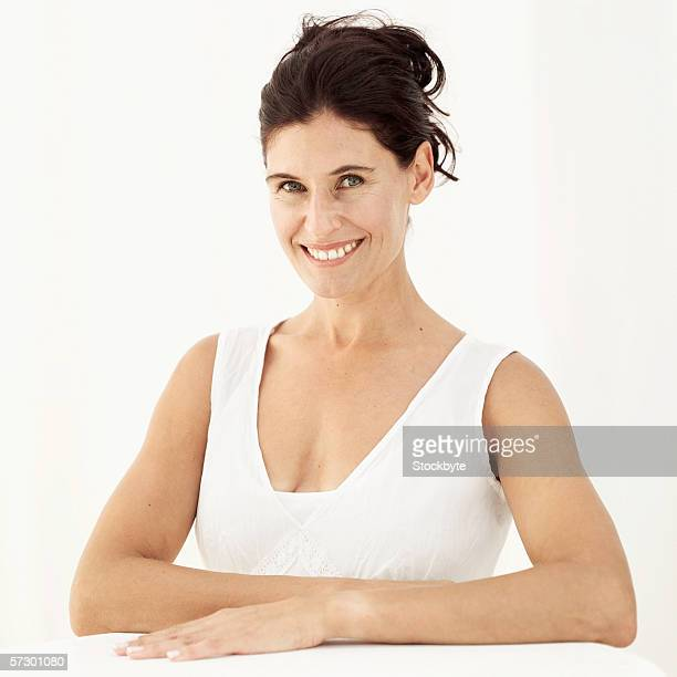 Portrait of a woman sitting with her hands on the table smiling