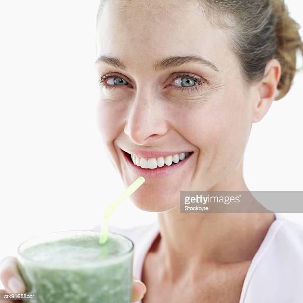 portrait of a woman smiling holding a glass of juice