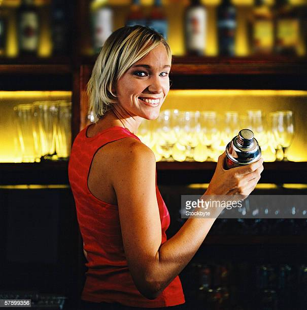 portrait of a woman standing at a bar holding a cocktail shaker