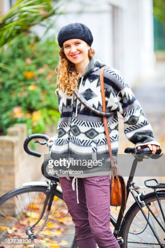 Portrait of a woman standing in front of a bicycle : Stock Photo