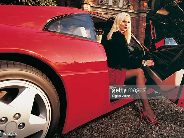 Portrait of a Woman Stepping Out of a Red Sports Car
