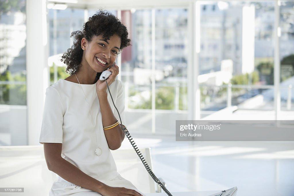 Portrait of a woman talking on a landline phone : Stock Photo