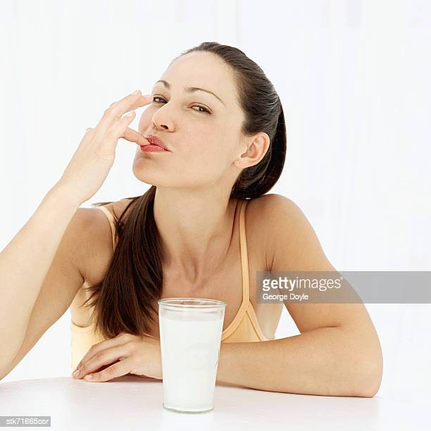portrait of a woman tasting milk with her finger