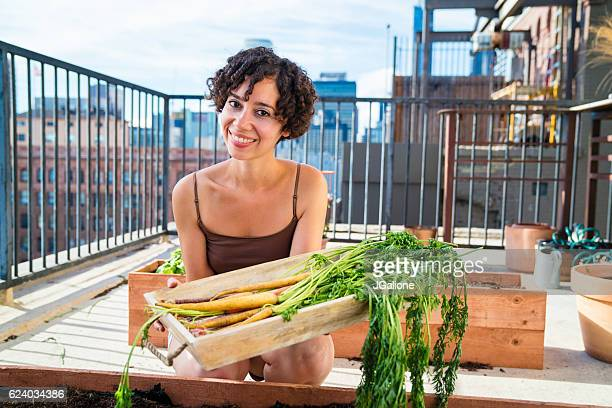 Portrait of a woman tending to her urban garden